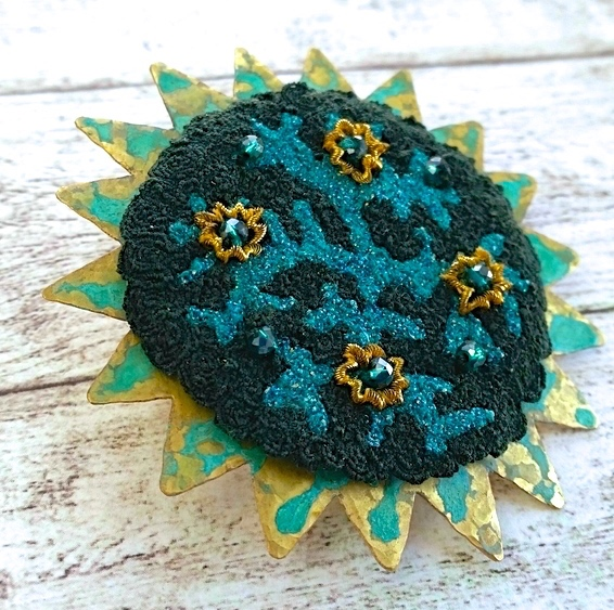 Embroidery embellished verdigris patinated brass brooch.