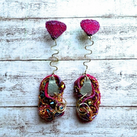 Embroidered sculptural earrings hanging from heart shape.