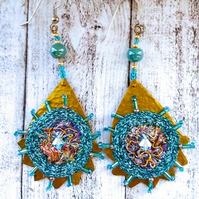 Textile embroidery and brass earrings.