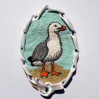 Stitched seagull ribbon edged oval brooch.