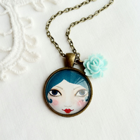 Doll Face Pendant With Blue Flower Charm