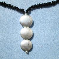 Black onyx chips necklace with silver puffy coin pendant.