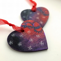 Heart shaped pair of handpainted Christmas decorations with red swirls