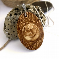 Sleepy fox cub in the woods, oval pyrography wooden pendant.