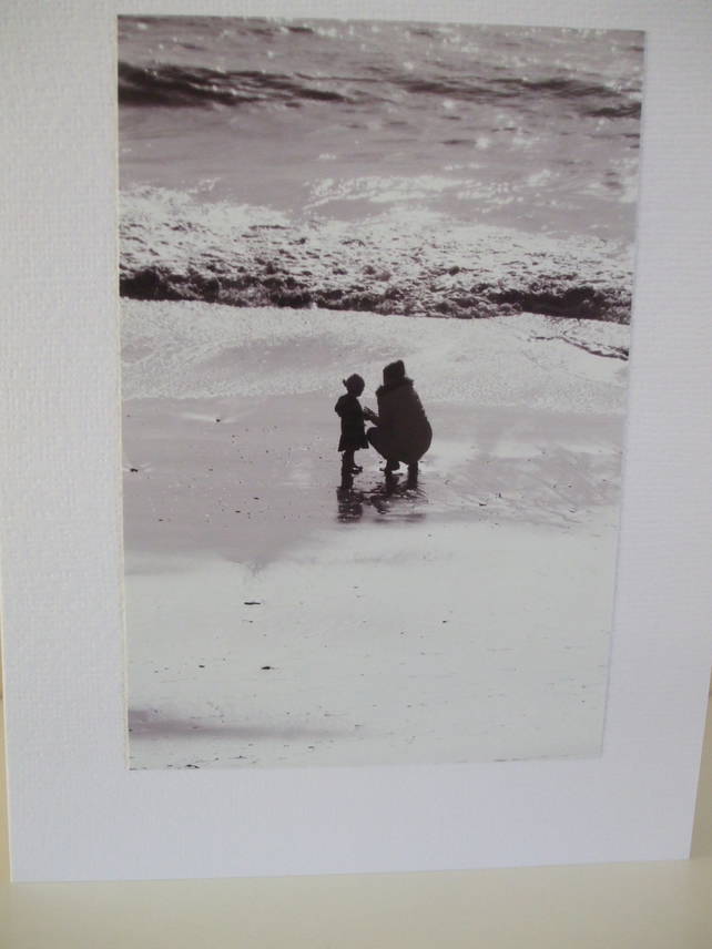 Black and white photo of a mother and child on a beach in Winter sunshine.