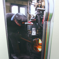 Photographic greetings card of a railway man working hard in the cab.
