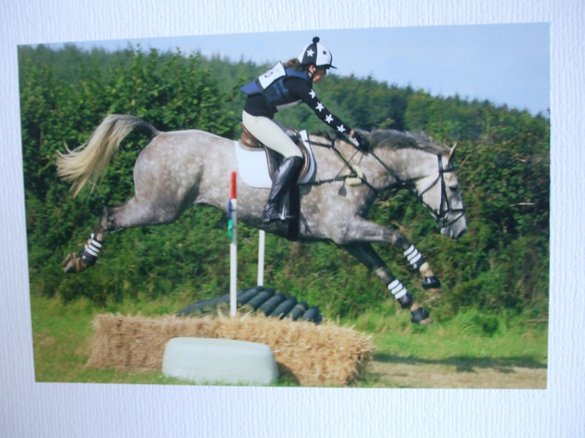 Photographic greetings card of a grey dapple horse and rider going over a jump.