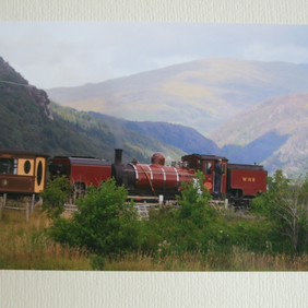 Photographic greetings card of a Welsh Highland Railway steam train in dark red.