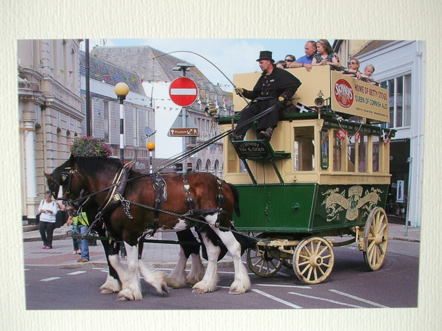Photographic greetings card of two horses pulling an open top bus.