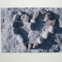 Landscape photographic card with pebbles in a heart shape.