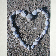 Photographic greetings card of pebbles in a heart shape on a beach.