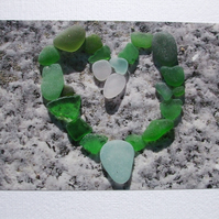 landscape photographic card of sea glass in a heart shape.