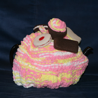Hand knitted tea cosy with felt biscuits and cakes