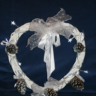 Large white wreath with ribbons, fir cones and white star lights