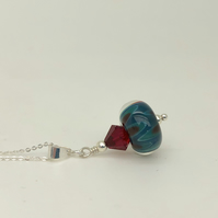 Turquoise and red lampwork glass pendant on adjustable chain. Sterling silver.