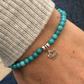 Turquoise stretch bracelet with silver lotus flower charm
