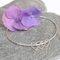 Sterling silver bangle with heart charms