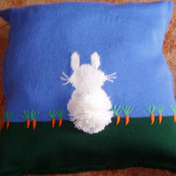 "Cushion with a rabbit design. Hand embroidered carrots and bobble tail. 18""."