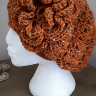 Ladies slouchy crochet beanie hat with large flower, in a rust autumnal colour
