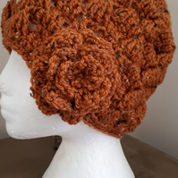 Ladies crochet beanie hat with flower, in a rust autumnal colour, chunky stitch