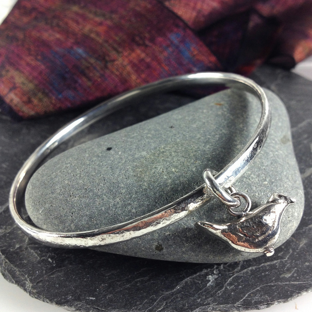 Solid silver round bangle with bird charm.