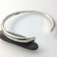 Heavy oval silver open bangle with notched detail