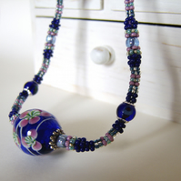 'Bottled blooms' Beadwork necklace with large glass focal bead