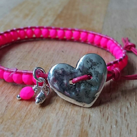 Neon pink glass bead and leather bracelet with heart button