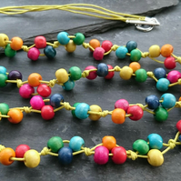 Rainbow coloured wooden bead necklace on yellow cotton cord