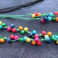 Rainbow wooden necklace on bright green cotton cord