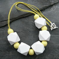White and yellow geometric wooden necklace with heart shaped toggle clasp