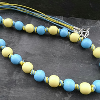 Blue and yellow wooden bead knotted necklace with heart shaped clasp