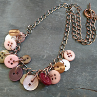 Button necklace with copper chain and toggle clasp, muted colours