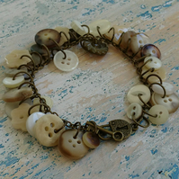 Cream mix button bracelet, antique gold chain and padlock shaped toggle clasp