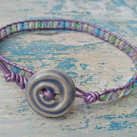 Lilac leather bracelet with mixed glass beads and ceramic button
