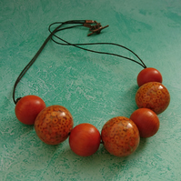 Orange chunky wooden necklace on brown cotton cord with copper toggle clasp