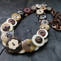 Button necklace in creams and browns with copper chain