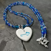Blue ceramic heart pendant with key decoration and beaded necklace