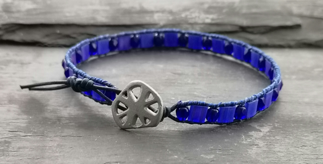 Blue leather bracelet with round and square glass beads and metal button