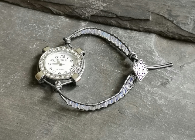 Sparkly silver coloured watch with opal and leather strap, button fastener
