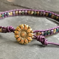 Purple leather bracelet with gold flower button and metallic finish glass beads