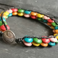 Black leather bracelet with rainbow coloured wooden beads and silver button