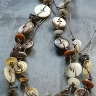 Long button necklace in creams and browns with a copper magnetic clasp