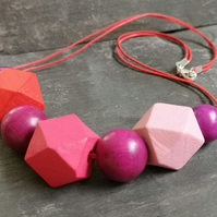 Necklace with berry coloured wooden geometric beads, trigger clasp, cotton cord