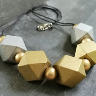 Necklace with gold and silver coloured wooden geometric beads, black cotton cord