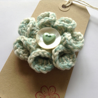 Green and white flower corsage with mother-of-pearl button