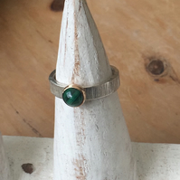 6mm Malachite set in 9 carat gold on textured wide silver band. Size L.5