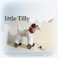 Tilly a little white dog on vintage Meccano wheels