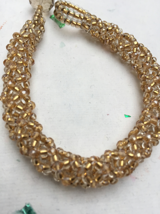 Pale gold crystal and seed bead netted bracelet with faceted rondelle bead clasp