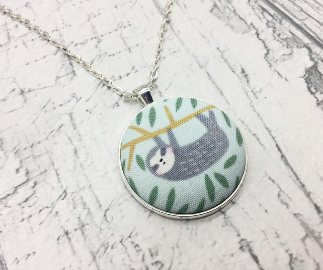 Sloth hanging or waving in a tree fabric button pendant